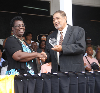 Lucia Wilkinson receives an award from His Honour Eustace John Deputy Governor General for her services in Education