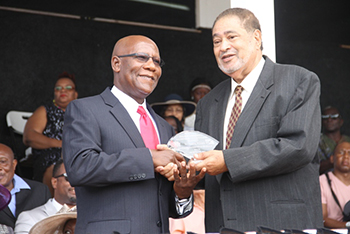 Stedroy Williams receives an award from His Honour Eustace John Deputy Governor General for his services in Health