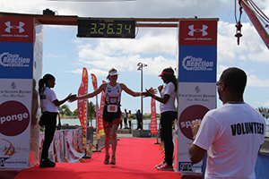 A winner in the first Macca X Nevis Triathlon in 2014, at the finish line while Tourism Minister Hon. Mark Brantley cheers her on (file photo)
