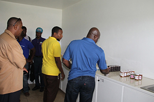 Minister of Agriculture on Nevis Hon Alexis Jeffers looks at products made at the Nevis Agro Processing Centre at Prospect on November 04, 2014, with Centre Manager Dwight Brown (left), Permanent Secretary in the Ministry of Agriculture Eric Evelyn (standing behind) and other officers of the Department of Agriculture looking on