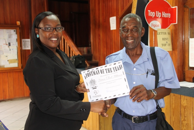 "Deputy Post Mistress General Rhonda Forbes-Williams presents ""Postman of the Year"" award for 2014 to Vernon ""Tim"" Wilkinson at the Post Office in Charlestown"