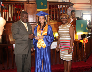 (L-R) Principal of the Charlestown Secondary School Edson Elliott presents Valedictorian Brianna Brantley with The Principal's Medallions Excellence Award while Presenter Mrs. Marva Roberts looks on