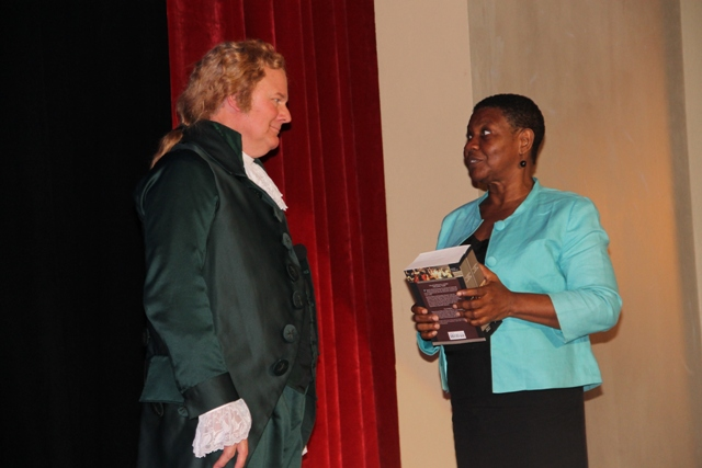 "Dr. William Bill Chrystal an Alexandra Hamilton impersonator Dr. William Bill Chrystal a world renowned Alexandra Hamilton impersonator presents Principal Education Officer Palsey Wilkin with copies of ""Plutarch's Lives"", a book read by Hamilton, after his performance at the Nevis Performing Arts Centre on Monday, November 24, 2014"