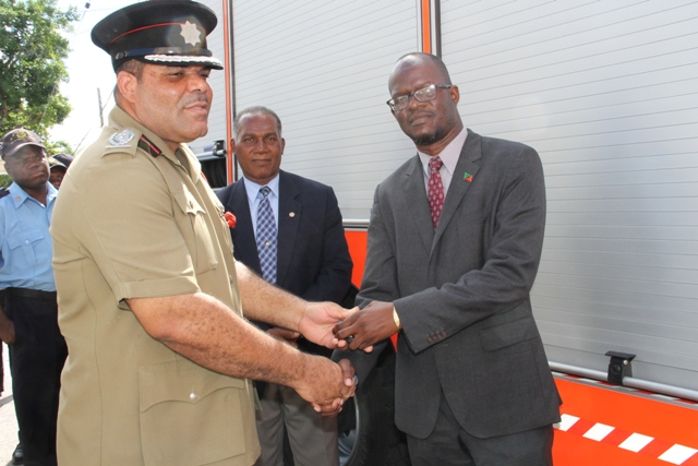 Acting Fire Chief Everette O'Garro receives keys to the new fire tender from Federal Minister of Homeland Security Hon. Patrice Nisbett at the Charlestown Fire Station on December 17, 2014. Premier of Nevis Hon Vance Amory looks on