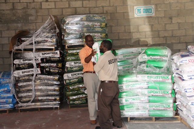Supply Office Manager Ricky Liburd assists a customer with a bag of dog feed on January 06, 2015