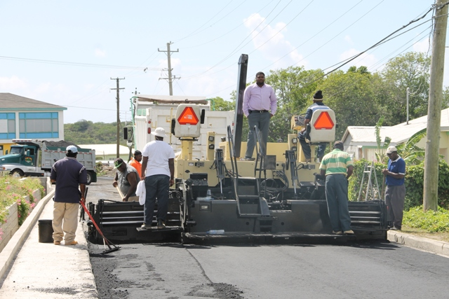 Junior Minister in the Ministry of Communications and Works Hon. Troy Liburd (standing on the asphalt paver) oversees final road works on the Charlestown Bypass. The road has since been renamed Stuart Williams Drive