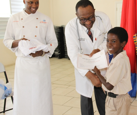 Head of the Rouse Foundation, Cardiologist Dr. Charlie Rouse and Celebrity Chef of Atlanta Marvin Woods, distribute Certificates of Participation and chef gear to students of the Charlestown Primary School for their participation in the Mini Chef Academy on February 24, 2015