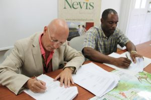 (L-R) Director of Caribbean Helicopters Ltd. (CPL) Neil Dickinson and Permanent Secretary in the Ministry of Finance in the Nevis Island Administration (NIA) Colin Dore sign the agreement between CHL and the NIA for the provision of airlift between Nevis and Antigua, at the Nevis Tourism Authority's Visitor Centre on February 13, 2015