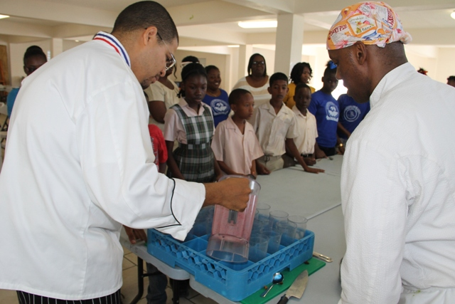 (L-R) Food and Nutrition Specialist attached to the School Meals Programme on Nevis, Executive Chef Michael Henville and Celebrity Chef of Atlanta Marvin Woods,   demonstrates to students of the Charlestown Primary School how to make healthy snacks at a Mini Chef Academy session at the school's kitchen on February 24, 2015