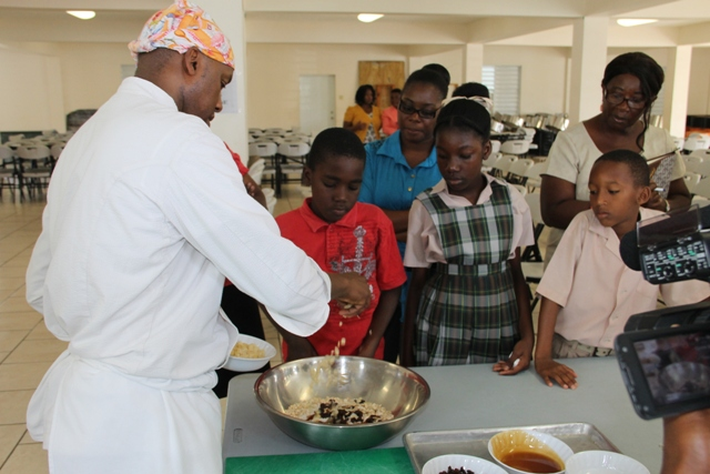 Students of the Charlestown Primary School look on at a Mini Chef Academy session as Celebrity Chef of Atlanta Marvin Woods demonstrates how to make healthy snacks at the school's kitchen on February 24, 2015