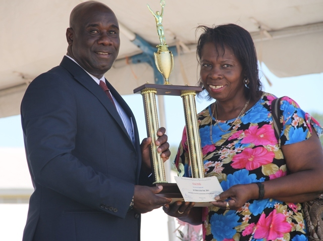 A family member of Top fisher in Nevis for 2014 Ehud Mills receives the Department of Agriculture award, on his behalf, from Minister of Agriculture Hon. Alexis Jeffersat the 21st Annual open Day hosted by the Department of Agriculture