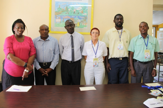 (L-R) Product Development Officer Nicole Liburd, Acting Permanent Secretary of Tourism Mr. Carl Williams, Policy and Regulations Officer in the Ministry of Tourism John Hanley and Taxi Drivers of the Queen City Taxi Association.