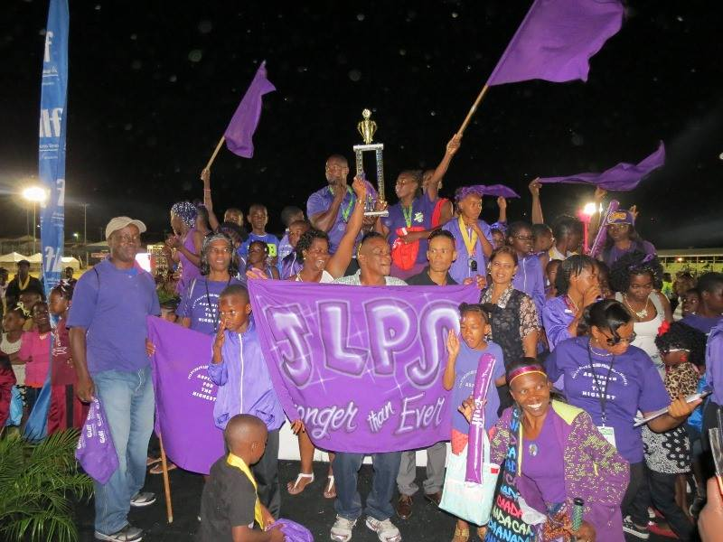 Athletes of the Joycelyn Liburd Primary School winners, of the 33rdGulf Insurance Inter-Primary School Champions celebrate with staff members and fans at the Elquemedo T. Willett Parkon April 01, 2015