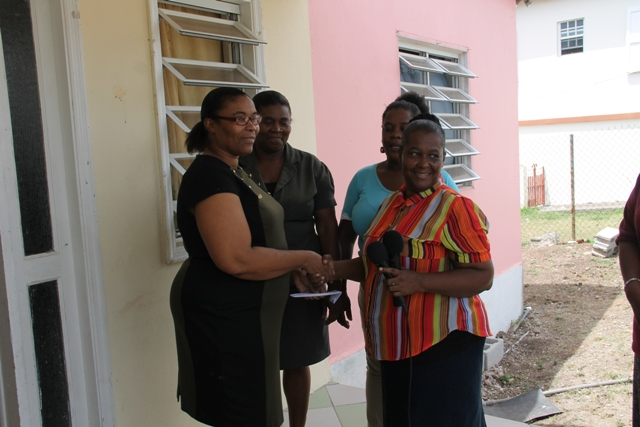 Gloria Pemberton of the Single Parents Group presenting Glenda Raymond with the monetary donation, on behalf of her husband Raymond Maynard