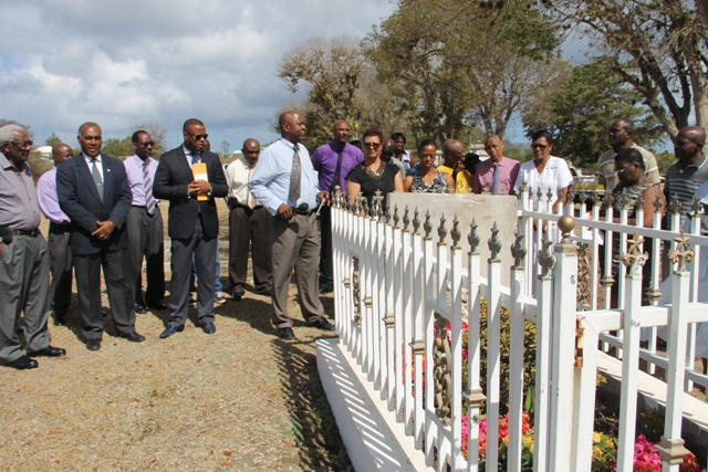 At the graveside of the late Malcolm Guishard at Bath Cemetery to honour his memory on June 11, 2015 are (front row l-r) Theodore Hobson, Premier of Nevis Hon. Vance Amory, Deputy Premier Hon. Mark Brantley, Cabinet Secretary Stedmon Tross, Widow of the late Malcolm Guishard Yvonne Guishard and their daughter Shanelle and Legal Advisor in the Nevis Island Administration Colin Tyrell