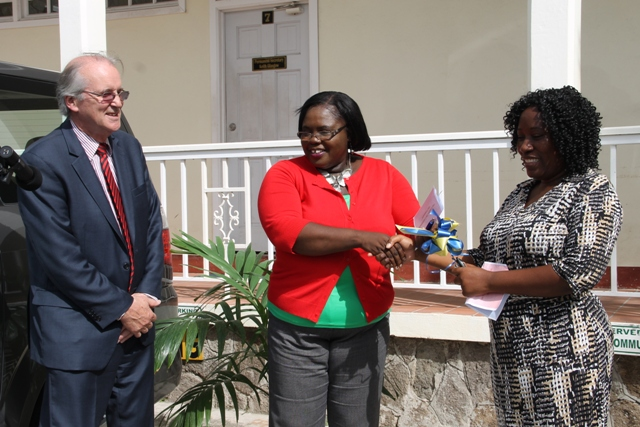 Minister of Community Development Hazel Brandy-Williams hands over keys to the new Suzuki, a gift from Trust Services (Nevis) Ltd. to Director of Community in the Department of Community Development Janette Maloney