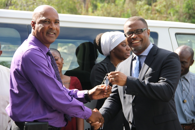 Minister of Culture in the Nevis Island Administration Hon. Mark Brantley handing over the keys of a new Toyota bus to Chief Executive Officer of the Nevis Cultural Development Foundation Keith Scarborough while the Foundation's staff looks on June 11, 201
