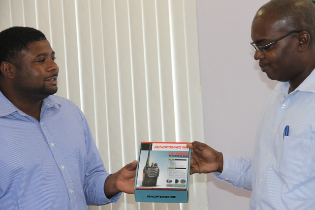 (L-R) Junior Minister in the Ministry of Communication and Works Hon. Troy Liburd handing over 12 BAOFENG short range two-way radios to Permanent Secretary in the Ministry of Communications and Works Ernie Stapleton at a handing over ceremony at the Nevis Island Administration's conference room, Charlestown on June 25, 2015