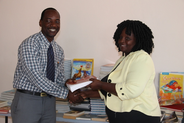 Assistant Secretary in the Premiers Ministry Kevin Barrett, handing over books to Principal of the Violet O. Jeffers Nichols Primary School Shae Wilkin during a handing over ceremony at the Franklyn Browne Community Centre held on July 29, 2015