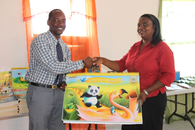 Assistant Secretary in the Premiers Ministry Kevin Barrett handing over books to Teacher at the Combermere Preschool Melisa Pemberton, during a handing over ceremony held at the Franklyn Browne Community Centre on July 29, 2015
