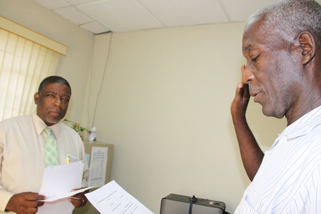 Calvin Fahie (r) being sworn in as a Registration Officer for Constituency 9 by Supervisor of Elections Elvin Bailey at the Electoral Office on Nevis on July 20, 2015