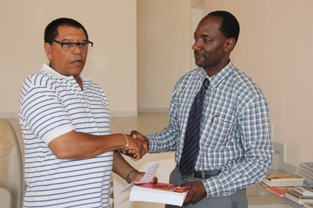 Chairman of The Combermere Reunion Committee Rumelo Jeffers presenting Assistant Secretary in the Premiers Ministry Kevin Barrett, with the books donated by Vincent Joseph, during a handing over ceremony held at the Franklyn Browne Community Centre on July 29, 2015