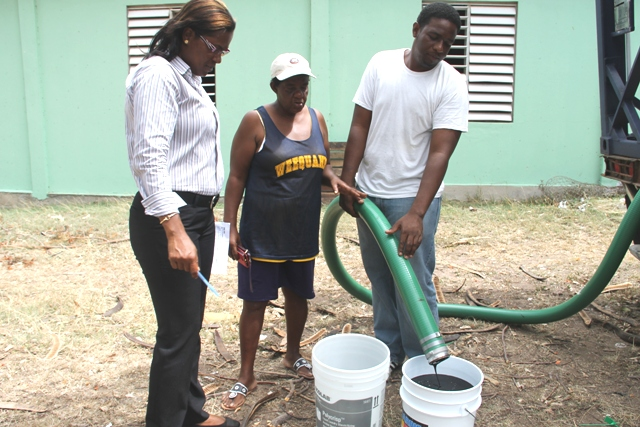 Supply Office staff Vera Brandy (left) and Tarron Slack (right) delivering molasses to livestock farmer Vera France of Camps Village at the Prospect Agricultural Station on June 07, 2015