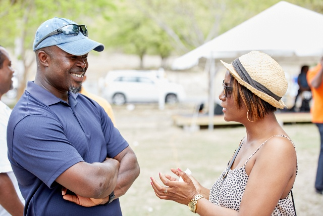 Chief Executive Officer of the Nevis Tourism Authority Greg Phillip speaking with a patron at The Nevisian Mango Feast on Oualie Beach on July 12, 2015. Photo by Refined Digital Media