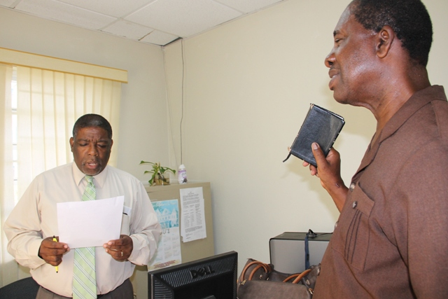 Nelson Stapleton (r) being sworn in as a Registration Officer for Constituencies 10 and 11 by Supervisor of Elections Elvin Bailey at the Electoral Office on Nevis on July 20, 2015