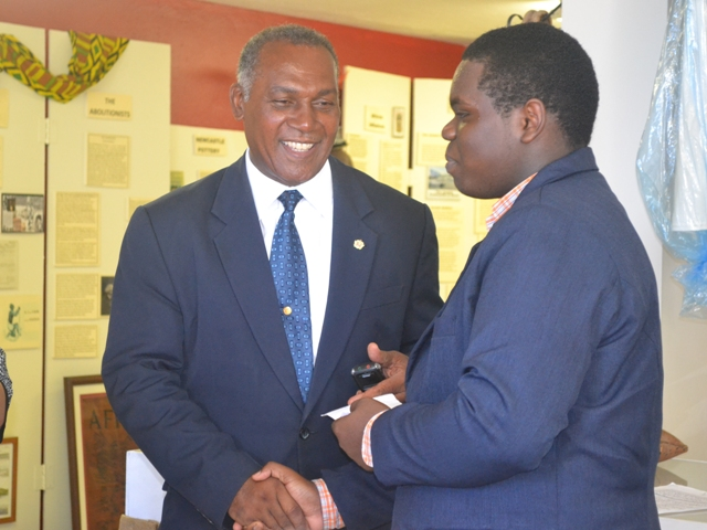 Premier of Nevis Hon. Vance Amory presenting Rol-J Williams with a monetary token from the Board of Directors and staff of the Nevis Historical and Conservation Society at their office on August 05, 2015, before travelling to Vermont in the USA to represent St. Kitts and Nevis at the 2015 Youth Ambassadors Program