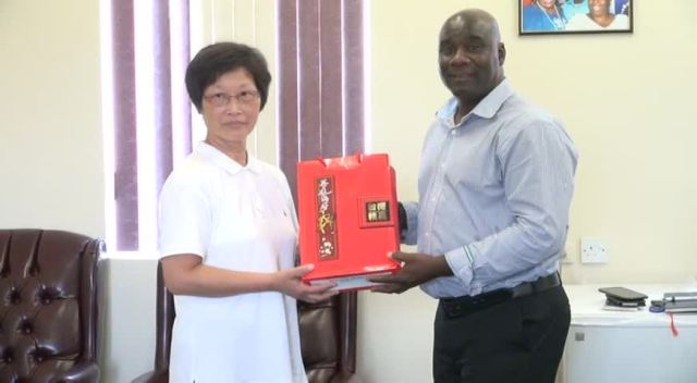 Minister of Agriculture on Nevis Hon. Alexis Jeffers presented with a gift from Crop Pest and Disease Control Specialist Tau-Mei Chou, a facilitator for the Pest and Disease Control and Soil Fertilisation Enrichment Workshop, hosted by the Republic of China (Taiwan) during a visit to his office on August 17, 2015