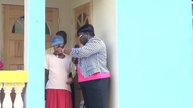 Junior Minister of Social Development on Nevis Hon. Hazel Brady-Williams hands over keys for a new home at Old Hospital Road to 84-year-old Estelle Bartlette on August 17, 2015