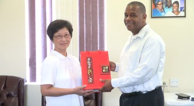 Permanent Secretary in the Ministry of Agriculture Eric Evelyn is presented with a gift from a facilitator for the Pest and Disease Control and Soil Fertilization Enrichment workshop hosted by the Republic of China/Taiwan, Crop Pest and Disease Control Specialist Tau-Mei Chou, on August 17, 2015