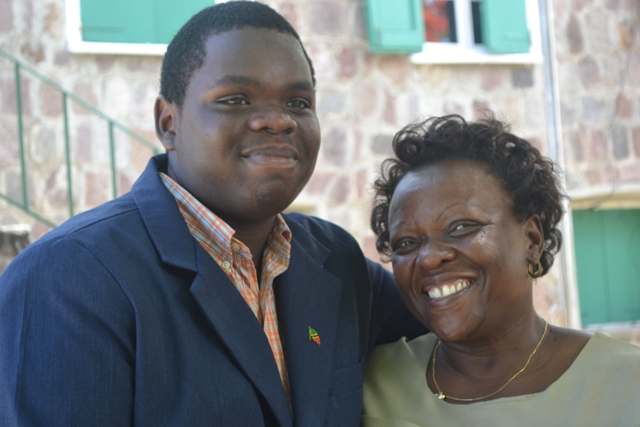 Rol-J Williams warmly embraces his mother Mrs. Janice Williams moments after he was honoured by Nevis Island Assembly President and Premier of Nevis Hon. Vance Amory at the Assembly grounds on August 05, 2015, for his achievement as a Youth Parliamentarian at the recent 40th Caribbean Parliamentary Association's (CPA) Caribbean, Americas and Atlantic Region's Conference in Tortola, British Virgin Islands