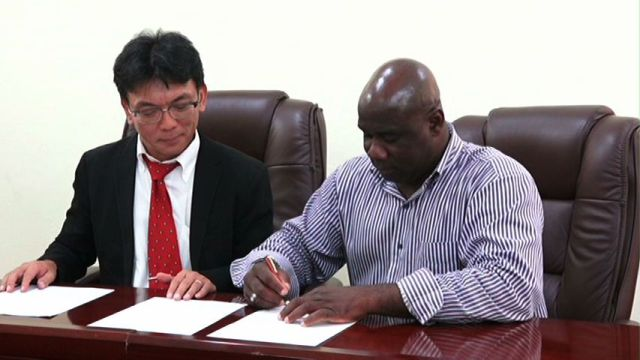 Minister responsible of Fisheries Hon. Alexis Jeffers signs an agreement to amend the grant agreement for the project for development of a Community Fisheries Centre in Charlestown at his Charlestown Office while General Manager of the JICA office in the Dominican Republic Morita Tatsuya looks on.