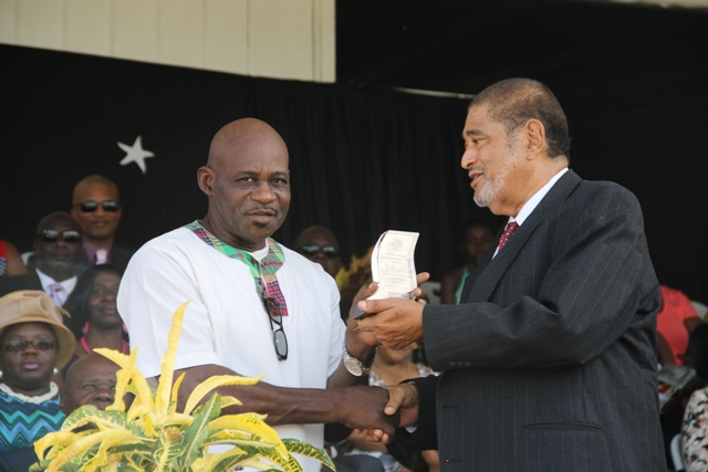 Former Police Officer Joseph Liburd receiving his award for his sterling contribution in the area of Law Enforcement from Deputy Governor General His Honour Eustace John at the 32nd Anniversary Independence Ceremonial Parade and Awards Ceremony at the Elquemedo T. Willet Park on September 19, 2015