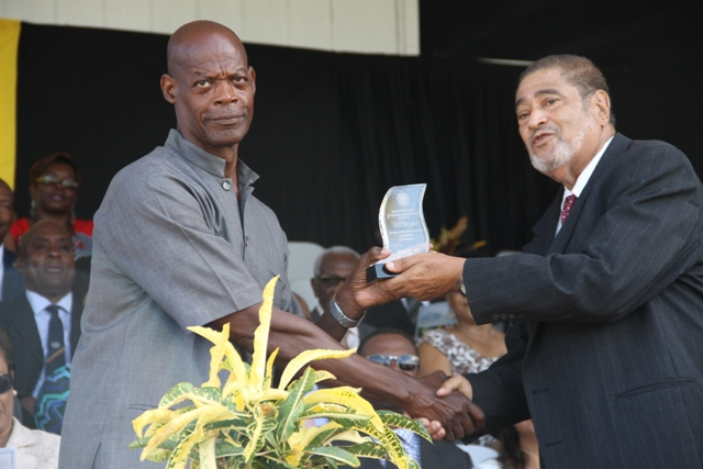 Former Police Officers Cecil Morgan receiving his award for his sterling contribution in the area of Law Enforcement from Deputy Governor General His Honour Eustace John at the 32nd Anniversary Independence Ceremonial Parade and Awards Ceremony at the Elquemedo T. Willet Park on September 19, 2015