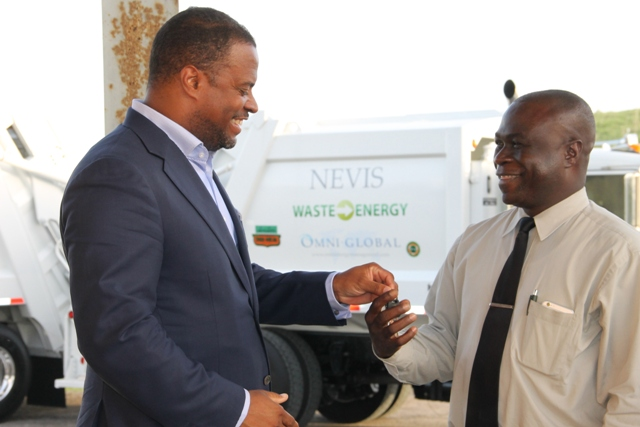 Deputy Premier and Minister of Health on Nevis Mark Brantley hands over keys to two state-of-the-art Kenworth garbage collection trucks to General Manager of the Nevis Solid Waste Management Authority Andrew Hendrickson at a handing over ceremony at the Long Point landfill on September 17, 2015
