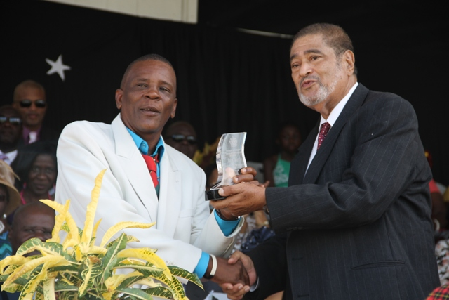 Ralph Allen receiving his award for his sterling contribution in the area of Culture from Deputy Governor General His Honour Eustace John at the 32nd Anniversary Independence Ceremonial Parade and Awards Ceremony at the Elquemedo T. Willet Park on September 19, 2015