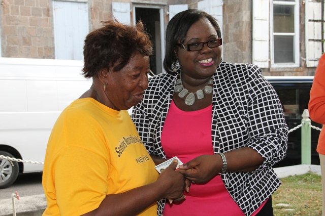 Junior Minister in the Ministry of Social Development Hon. Hazel Brandy-Williams handing out an official identification card for the Ministry's Seniors Subsidized Transportation Programme to one of the 150 seniors registered for the programme