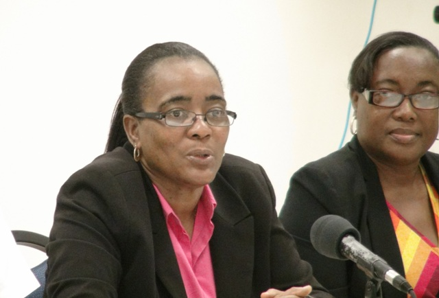 (L-R) Head of the Small Enterprise Development Unit in the Ministry of Finance Catherine Forbes and facilitator Alexa Pemberton during the closing ceremony for the Small Enterprise Development Unit's Quick Books Accounting workshop with a certificate of completion at the Nevis Disaster Management Department's conference room at Long Point on October 23, 2015