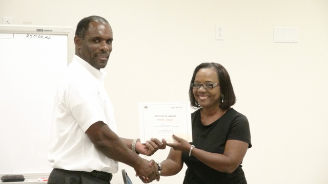 Permanent Secretary in the Ministry of Finance Colin Dore presents one of 13 participants in the Small Enterprise Development Unit's Quick Books Accounting workshop with a certificate of completion at the Nevis Disaster Management Department's conference room at Long Point on October 23, 2015