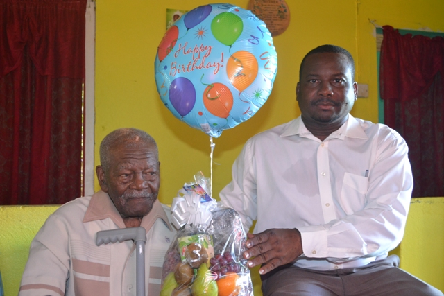 Butlers Villager Mr. William Douglas celebrating his 101 birthday is presented with a fruit basket from Permanent Secretary in the Ministry of Social Development Keith Glasgow on behalf of the Ministry at his home in Butlers Village on October 08, 2015