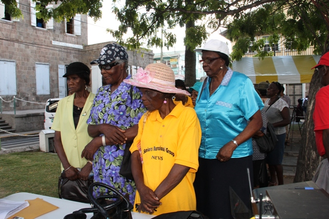 Seniors line up to receive their identification cards for the Ministry of Social Development's Seniors Subsidized Transportation Programme which was launched at the Memorial Square in Charlestown on October 01, 2015