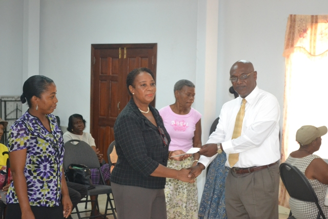 Director of the Nevis Corporative Credit Union Board Vernel Powell, presents a cheque on behalf of the Credit Union to Coordinator of the Seniors Division in the Ministry of Social Development Garcia Hendrickson for the care of seniors on Nevis at St. Paul's Conference Hall on October 12, 2015 while Senior Social development Officer Sherilyn Liburd looks on