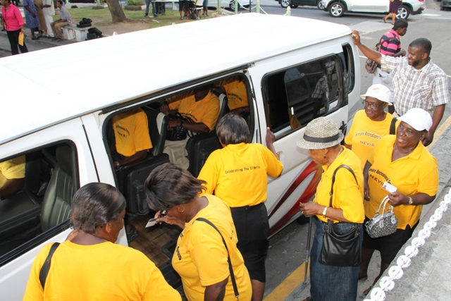Some senior citizens boarding a public bus with the Nevis Bus Association logo after they received their identification cards on October 01, 2015, as part of the Ministry of Social Development's Seniors Subsidized Transportation Programme