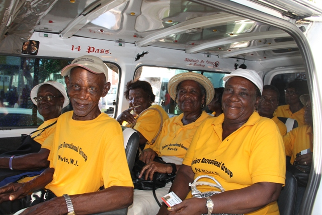 Seniors board a Nevis Bus Association vehicle for free travel on October 01, 2015, moments after the Ministry of Social Development's Seniors Subsidized Transportation Programme was launched at the Memorial Square in Charlestown