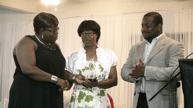 Junior Minister in the Ministry of Social Development Hon. Hazel Brandy-Williams presents award for Worker of the Year 2015 in the Nevis Social Services Department Seniors' Division to Glorita Vaughn at the 3rd Annual Gala and Awards Ceremony hosted by the Department of Social Services Seniors Division at the Occasions Conference Centre on October 27, 2015. Permanent Secretary in the Ministry of Social Development Keith Glasgow looks on