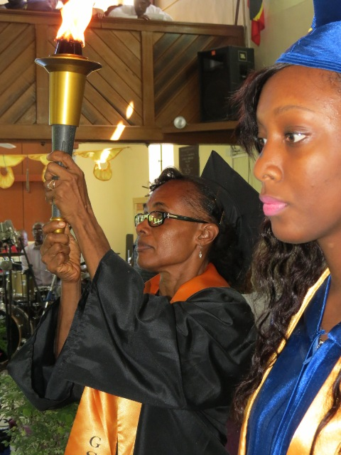 Derez Morton Valedictorian of the Gingerland Secondary School's Graduating Class of 2015 awaits the torch from Deputy Principle Lineth Williams at the 42nd annual Graduation Ceremony at the Gingerland Methodist Church on November 12, 2015