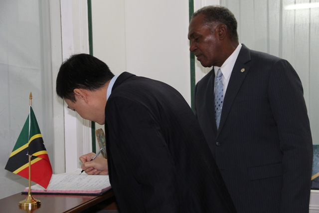 Minister Counsellor in the Vietnam Embassy Mr. Duong Hai Hung signs the visitor's register at the Premier's office on November 24, 2015, while Premier of Nevis Hon. Vance Amory looks on